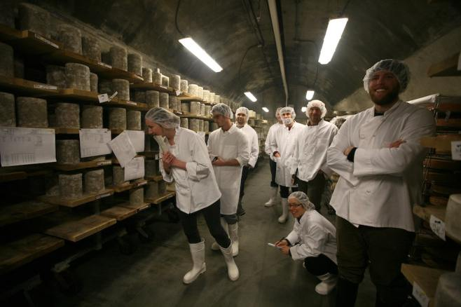 a group of people in white coats and hairnets in a cheese cave