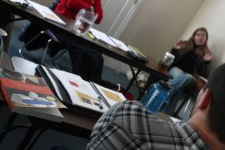 a group of people seated in a classroom with cheesemaking books on the table