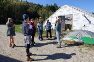 a group of people standing outside a greenhouse