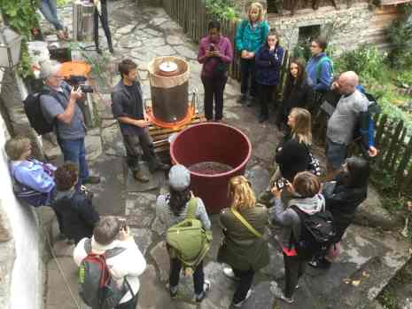 a group of people standing around a wine press