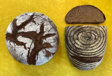 two loaves of fresh bread with decorative tops, one is sliced open