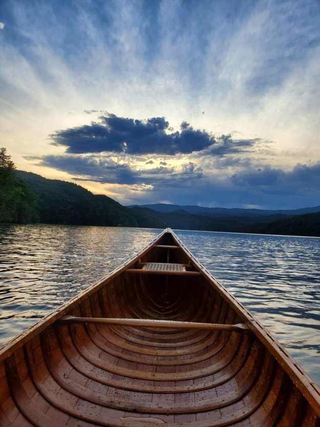 A photo of the Horace Strong canoe, taken at sunset from someone sitting inside the canoe, the view is of the lake. In the background is an island and mountains. Sunburst at sunset on the horizon.