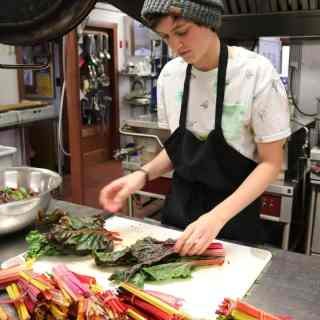 Student Kali stands at the counter in the Sterling Kitchen, wearing a black apron, preparing colorful rainbow chard for a meal.
