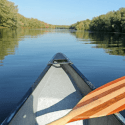 Front of canoe with a striped paddle across gunnels. River with reflection of green trees on edges, blue sky above.