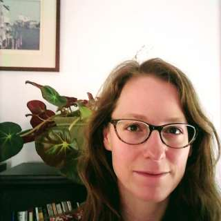 Elizabth is wearing glasses and poised in front of a houseplant.