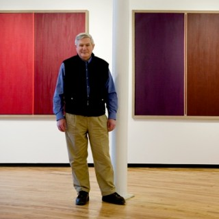 Paul is wearing khaki pants, a blue button down, and a dark vest. He is standing in front of two of his abstract art pieces.
