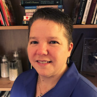 Lori is wearing a blue blouse and sporting a short haircut; she stands in front of a bookshelf.