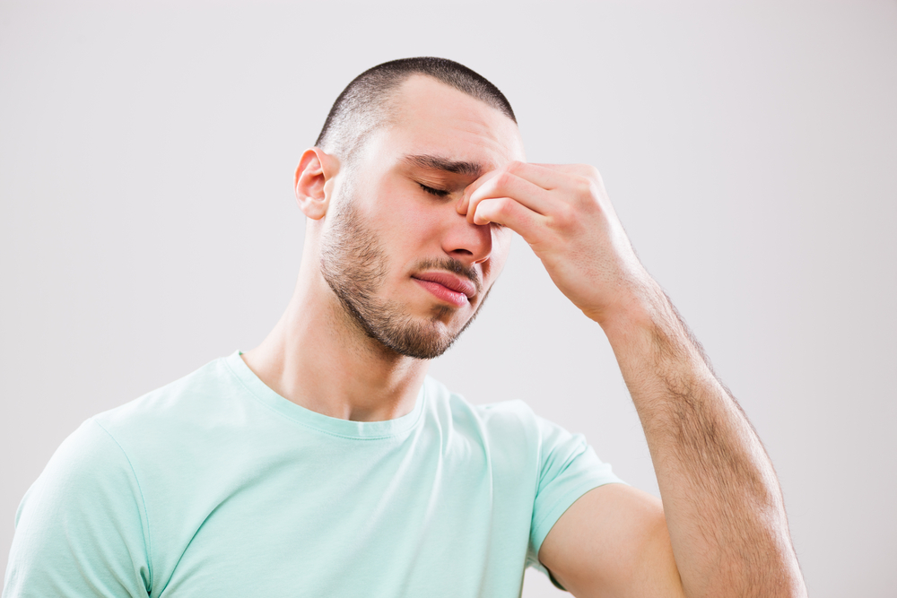 young man who is having pain in his sinus