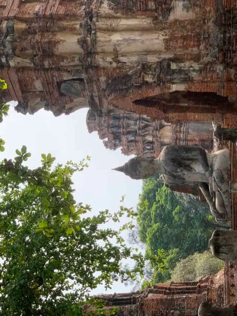 Buddha in the courtyard surrounded by many headless and ruined statues