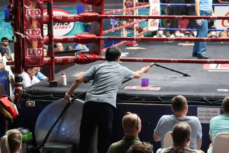 A worker cleans up water and ice that have landed on the ring mat after a rest break.