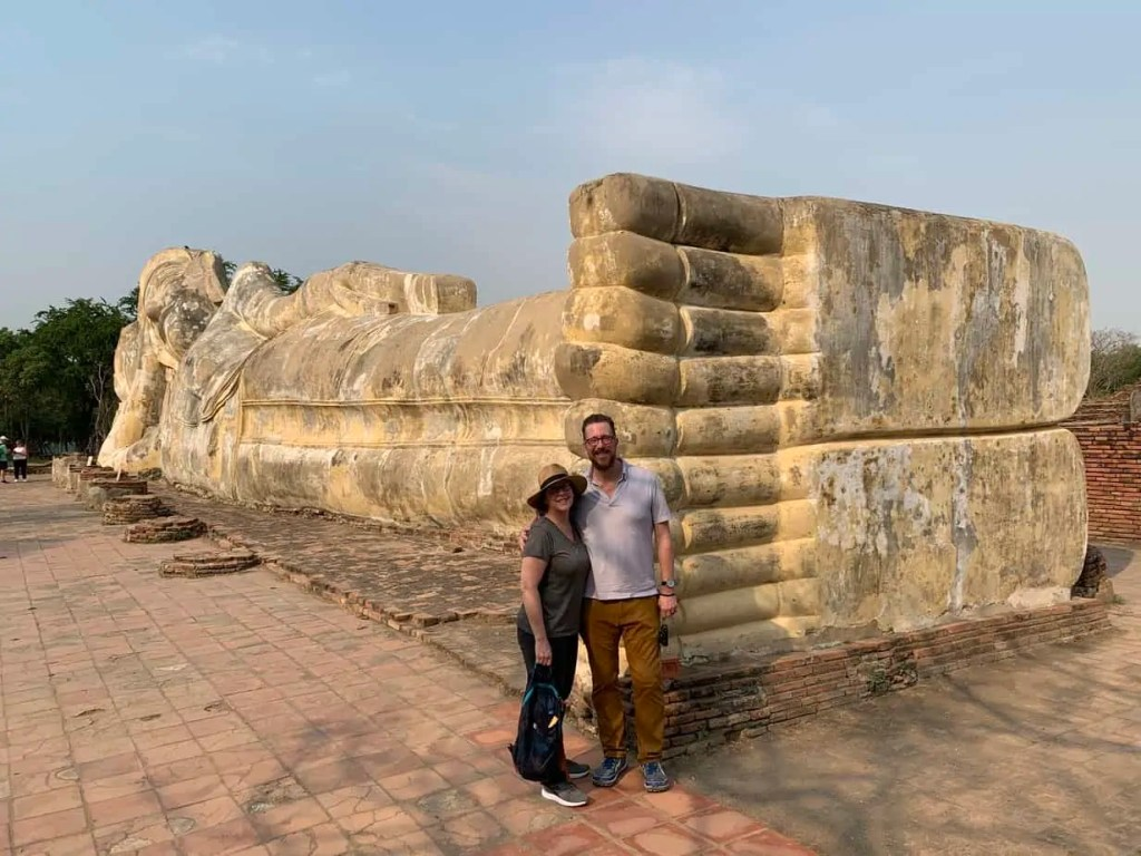 Steve and Noelle posing at the reclining Buddhas feet