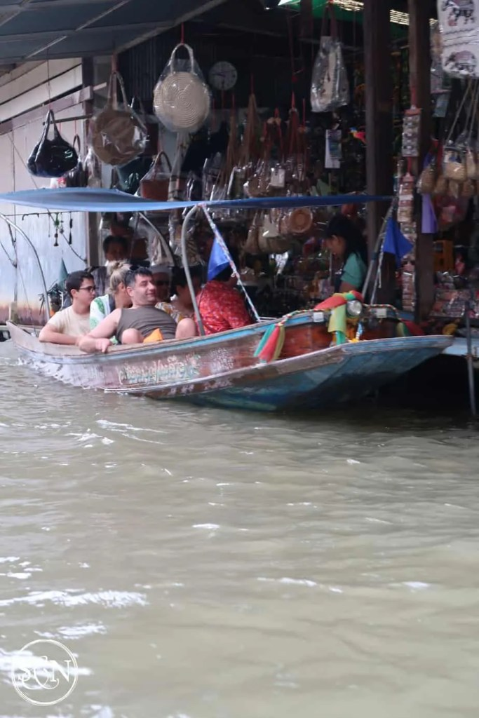 Buying purses at a dockside shop. Pull your boat right up. Jump in and see the market.