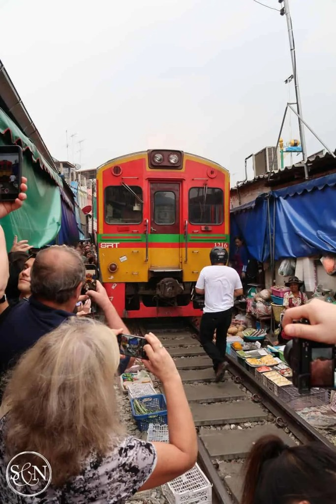 The train is slowing making its way into the Maeklong Railway Station