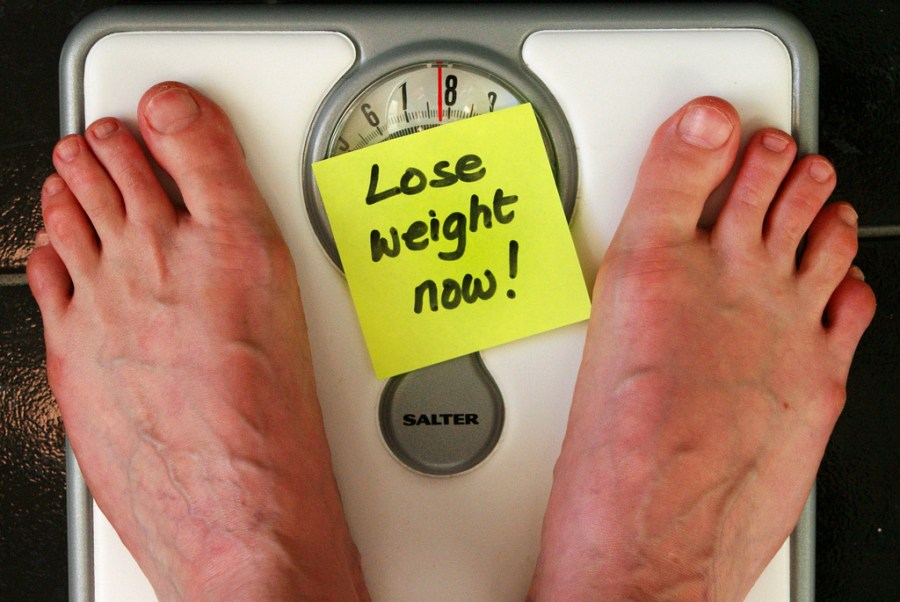 """A man's feet on a scale where a sticky-note reads """"Lose Weight Now"""""""
