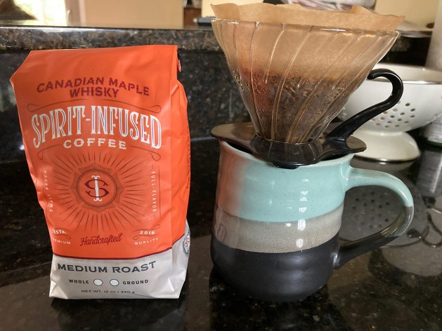 A bag of Fire Department Coffee's Maple Whiskey infused coffee next to a pour-over being made