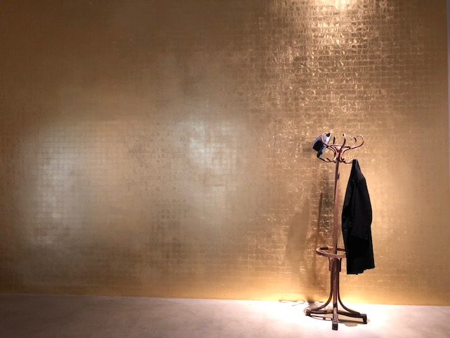 A hat and coat on a coat rack against a bare gold leaf wall