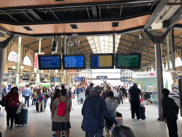 Inside the station, with displays showing departures, and train platforms behind it