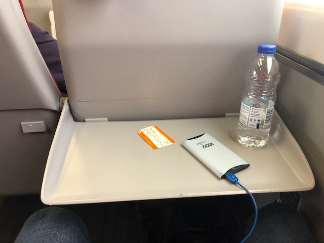 Train ticket, portable charger, bottle of water on the pull down tray