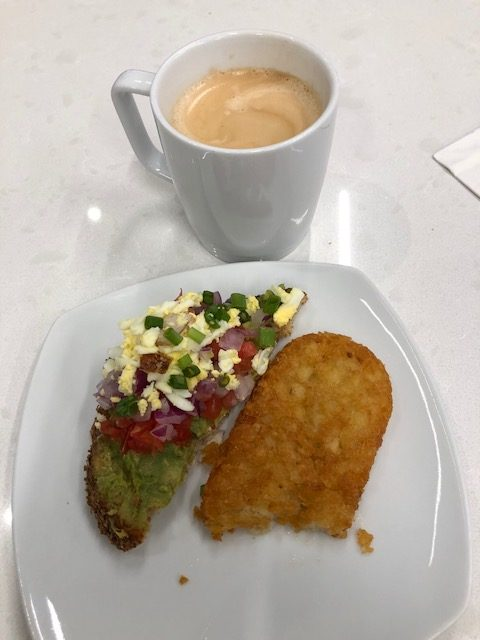 Coffee, avocado toast, fried hash brown patty