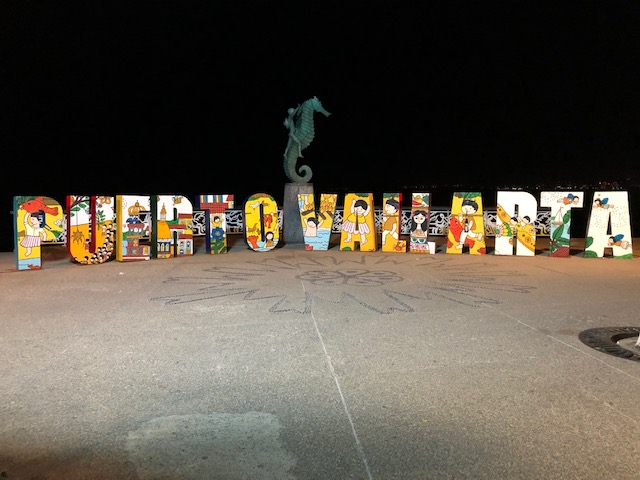 The Puerto Vallarta sign on the Malecon, with the bronze sculpture in the middle of a boy riding a seahorse