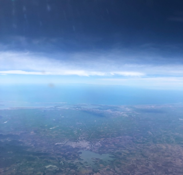 Mexican landscape from the plane, with the Gulf of California in the middle background and dark clouds above. Lots of shades of blue in this photo.