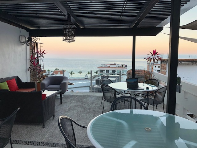 Several round glass tables with charis, and a couch with a couple of chairs next to it, with a view of the bay in the background. All open air, although covered.