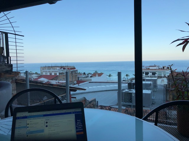 The top of my laptop in the bottom left corner, on a glass table, with the bay view in the background past red tile rooftops
