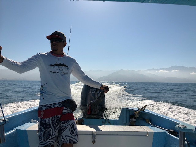 The driver of the boat, with a strong white wake shooting up from the outboard motor behind him