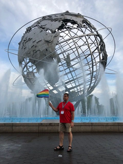 Me at the Unisphere waving a Pride flag