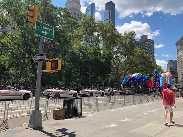 Street sign at 26th St & 5th Ave with a huge balloon arrangement up front, and vehicles participating as grand marshal behind it
