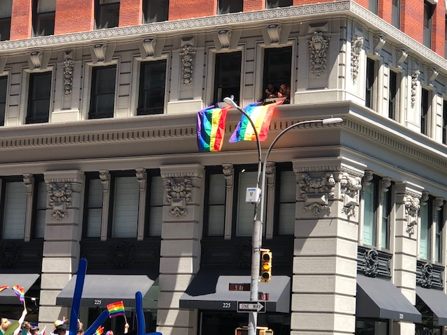 Rainbow flags draped from 2 windows on the 2nd floor of a building at the start, people watching from there