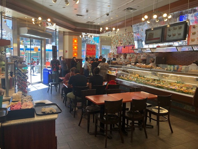 The dining area of Europa Cafe, with the workers behind a refrigerated food case