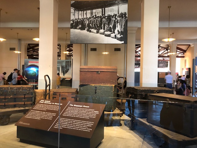 A display of trunks, probably 12 feet wide, with a black and white photo of immigrants lined up with their luggage above it