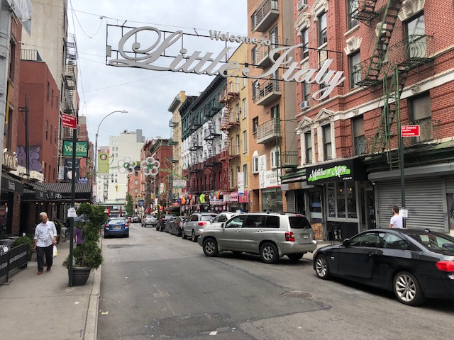 """Photo of a street with """"Welcome to Little Italy"""" sign going across it"""