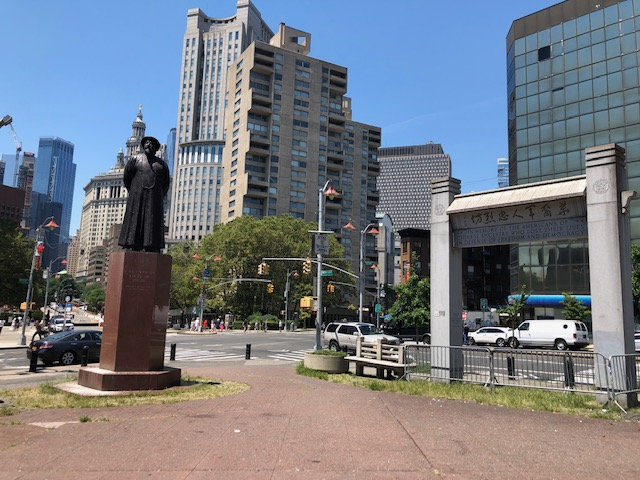 A statue of a man and an arch of sorts, at an intersection, tall buildings in the background