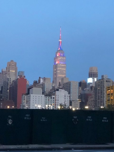 Top portioin of the Empire State Building lit in red, white and blue