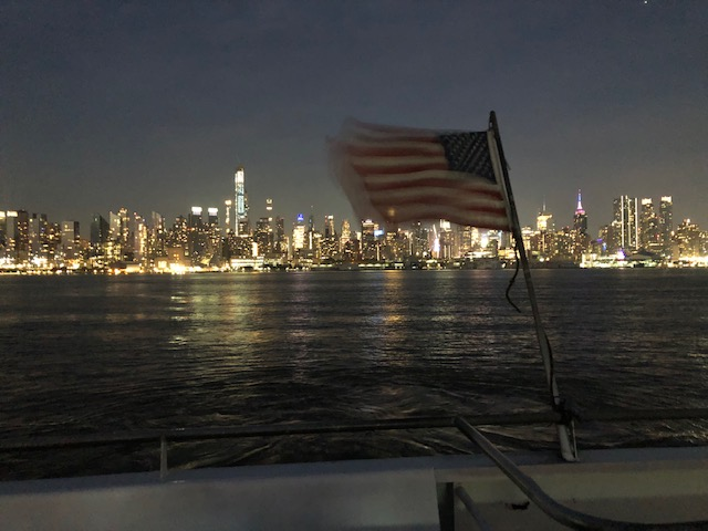 Midtown at night from the Hudson river, with a USA flag waving off the back of the boat