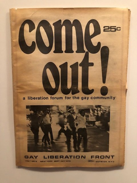"""An old pamphlet of the Gay Liberation Front, with """"come out"""" on the cover taking up half of it, with a photo underneath of policy taking people away in handcuffs"""