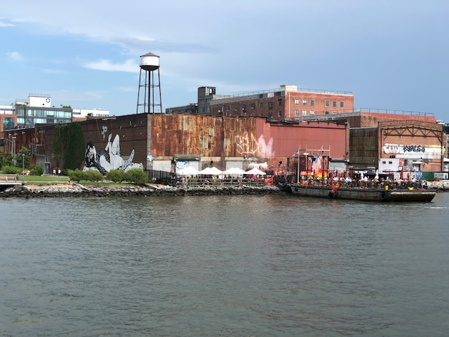 A bar on the river bank, at the end of the building the mural is on, which extends onto a barge on the water
