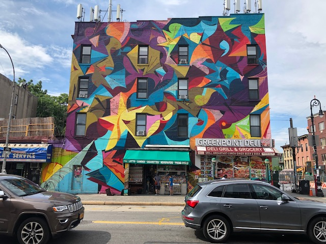 A very modern mural covering a square building 4 stories high, no discernible design excetp for a yellos start bottom left. Other colors include lime green, purple, orange, sky blue. There's a deli at the right bottom corner.