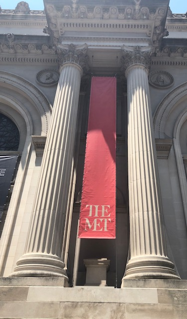 A tall banner with just the works The Met on it, in the middle of two columns, at the outside entrance