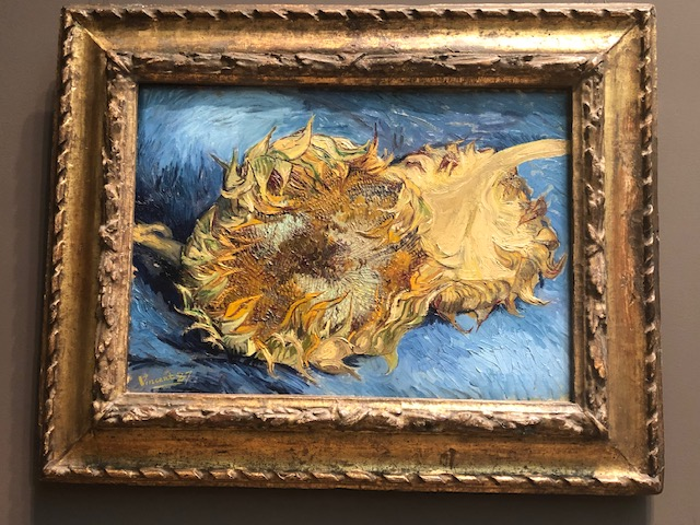 A huge sunflower facing you, takes up almost 2/3 of the canvas, with another upside down behind it