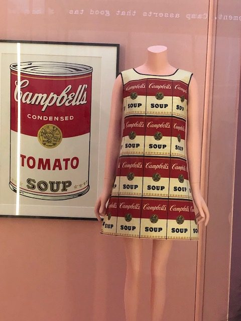 Andy Warhol type painting of a Campbell's soup can; and a slim mini dress with the soup can image all over, 4 rows of them.