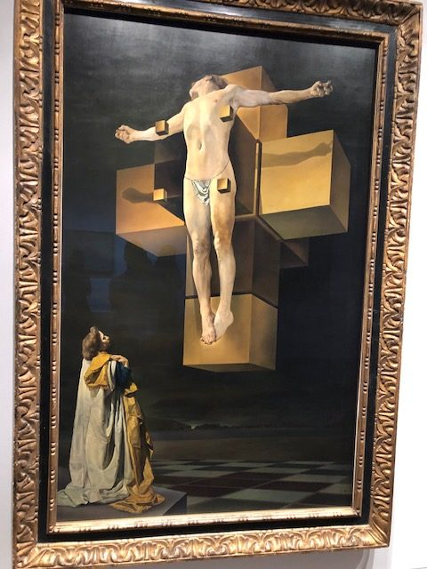 A healthy looking but naked Christ levitating in front of a cross that's cube-line in form