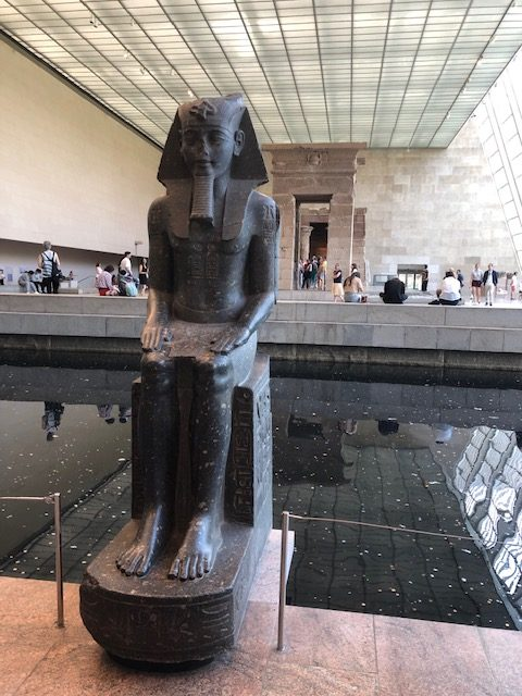 Statue of a pharoah, with a pool of water behind it, temple ruins behind that