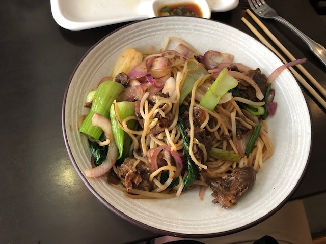 A beef and noodle stir fry with bok choy and onions