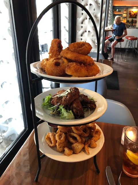 a 3 plate tower of appetizers in a black iron frame