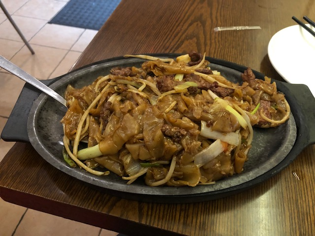 Sizzling spicy beef chow fun: beef, noodles, onions, peppers, served on a hot skillet