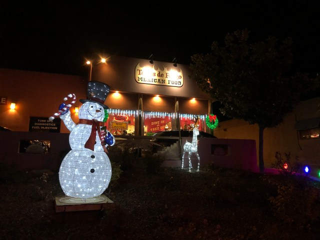 outside of the restaurant, small, simple, with a lighted snowman and reindeer in front and christmas lights on the building