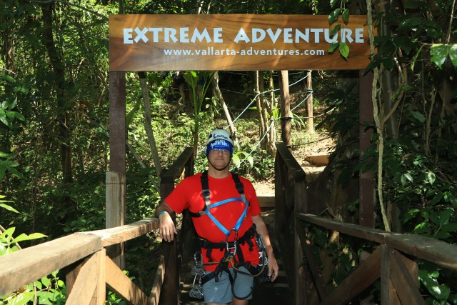 me standing below the Extreme Adventure sign, wearing all the gear for ziplining and rappelling